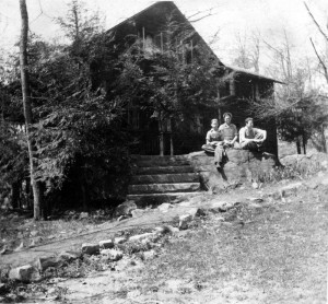 Farm House - Exterior view with 3 students on boulder in front of house; 1940s.