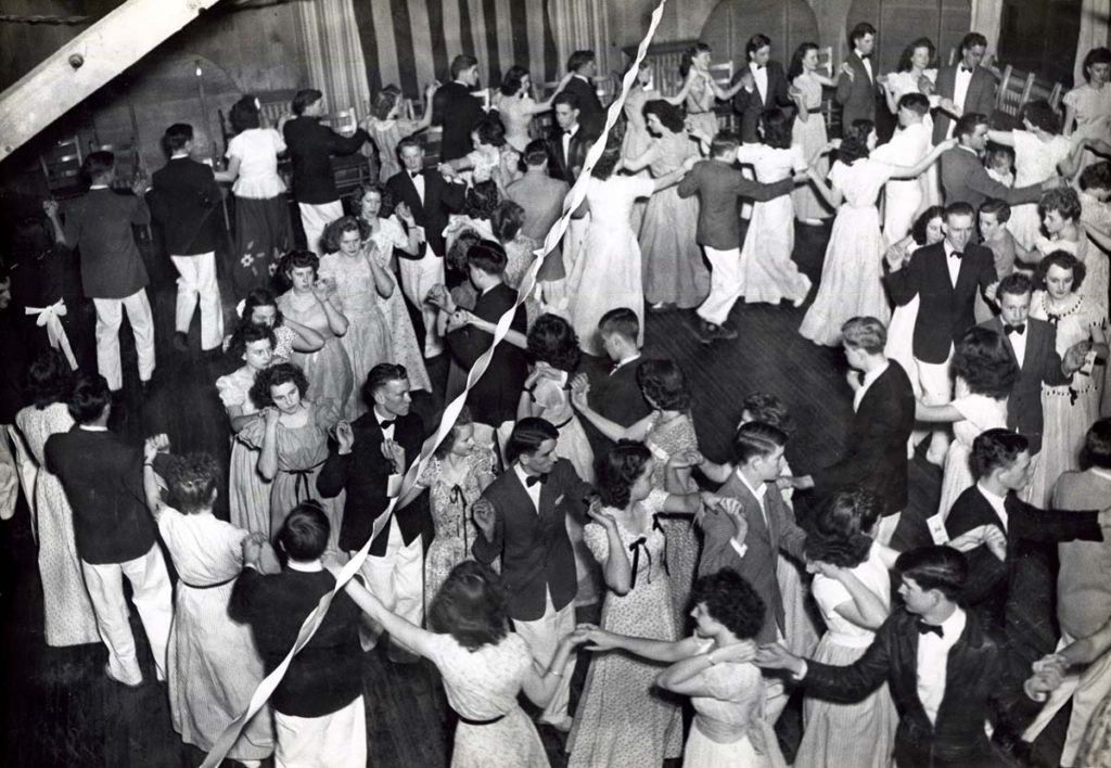 Black-and-white photograph of a ballroom filled with dancers in formal attire.