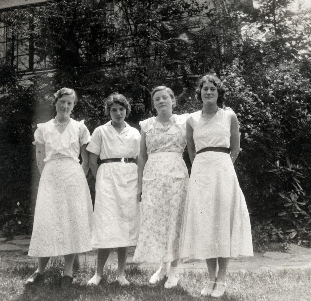 Four young women in dresses, including Polly Turner.